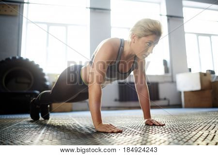 Having intensive fitness training in spacious gym: young blond-haired woman looking away with concentration while doing push-ups on floor