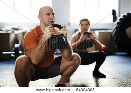 Young sporty woman and middle-aged bodybuilder doing kettlebell squat exercise during intensive training in gym
