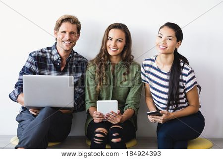 Portrait of business people sitting on seat against wall in office