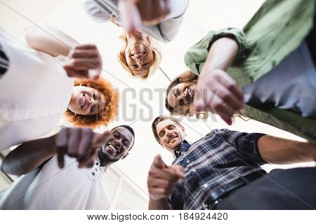 Directly below portrait of happy colleagues gesturing while standing against ceiling in office