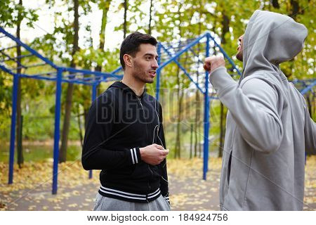 Profile view of two sporty men chatting animatedly with each other while warming up in autumn park, waist-up portrait