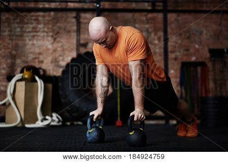 Tattooed sporty man doing push-ups with help of kettlebells while having training in modern gym, full-length portrait