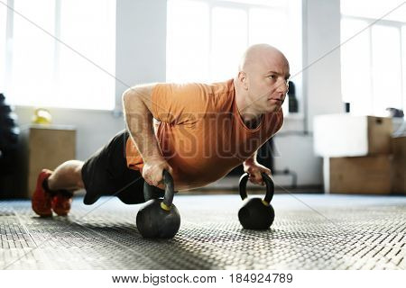 Concentrated fit man doing push-ups with kettlebells against white wall with panoramic windows of modern gym, full-length portrait