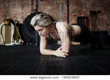 Blond-haired sporty woman doing plank exercise while having workout in modern spacious gym, full-length portrait