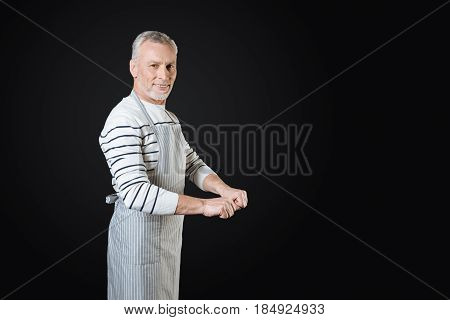 Wait a minute. Gray-haired male person turning his head to camera standing over black background making fists