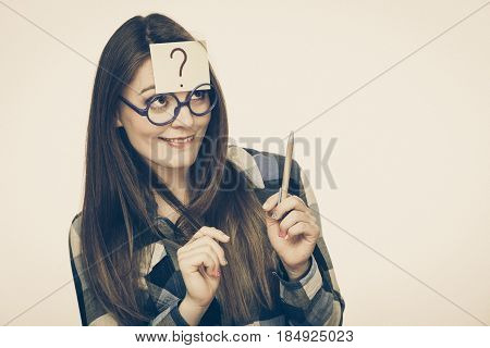 Woman confused thinking seeks a solution paper card with question mark on her head. Doubtful young female in glasses studio shot toned image