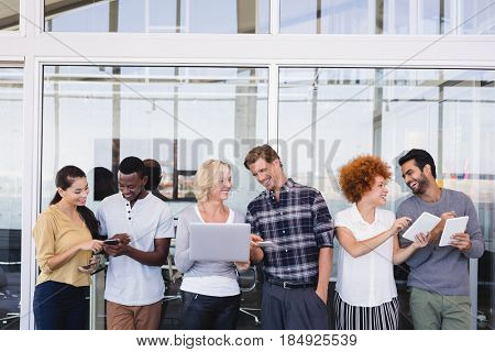 Business people using technologies while discussing against glass wall in balcony
