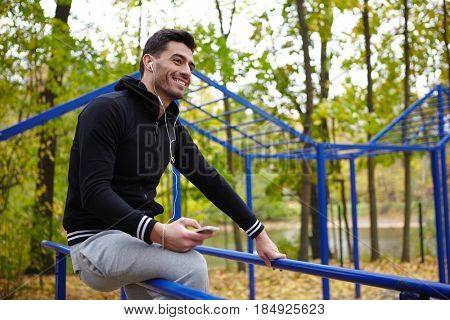 Cheerful young sporty man in headphones sitting on parallel bars in autumn park while taking short break during training