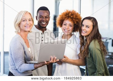 Portrait of happy colleagues with laptop standing in office