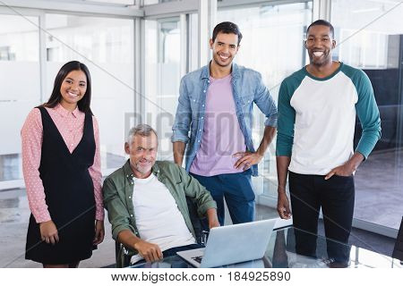 Portrait of smiling business colleagues at desk in boardroom