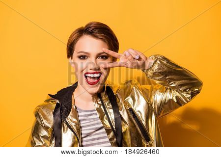 Playful Excited Fashion Model With Red Lipstick, Open Mouth, Gesturing And Shoving V Sign. She Is In