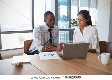 Businesspeople Working On Laptop In Boardroom Together
