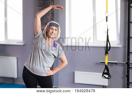 Physical activity. Joyful nice aged woman holding her hand up and bending while doing a physical activity