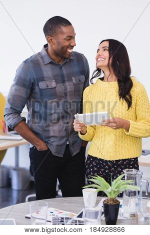 Happy business people discussing over tablet pc while standing in office