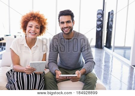 Portrait of smiling business colleagues with tablet pcs sitting on sofa in office