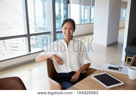 Portrait Of Businesswoman Using Digital Tablet In Boardroom