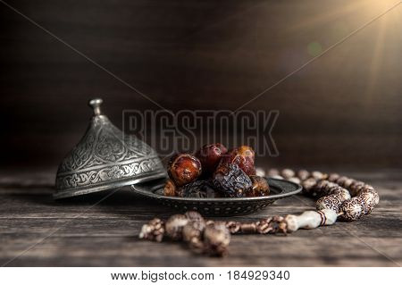 Date-palm Is Placed On Silver. Date Palm Fruits Or Kurma, Ramadan On A Wooden Black Background.