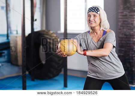 Sports activity. Delighted well built active woman holding a ball and working out with it while doing sports activities