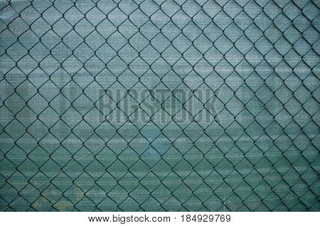 Green metal grid with a back green background