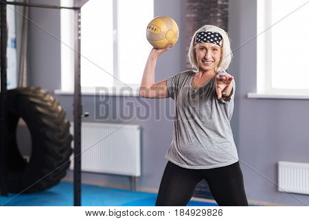 Exercises with a ball. Happy aged nice woman holding a ball and looking at you while doing physical exercises