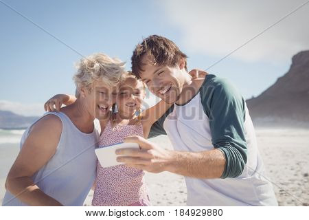 Happy multi-generated family taking selfie at beach during sunny day