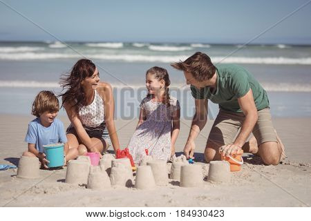 Cheerful family making sand castle at beach during sunny day