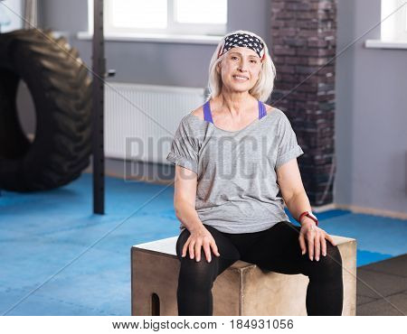 Minute to rest. Pleasant well built aged woman sitting on the wooden box and resting while being in the positive mood