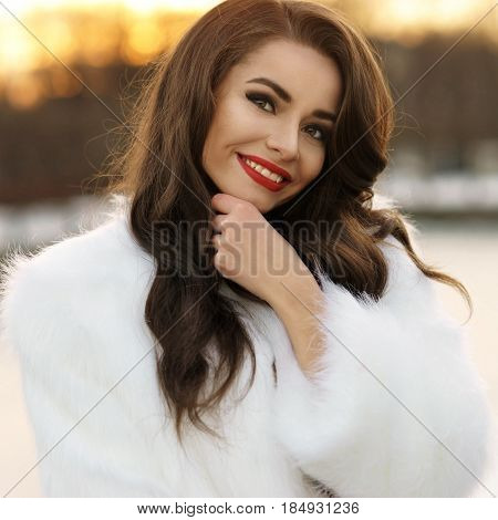 Closeup breast portrait of young beautiful caucasian woman with long wavy dark hair and red lips smiling and posing in white fur coat on cold winter day at sunset outdoors.