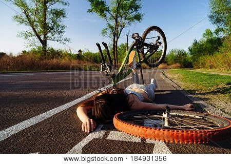 Girl fell from bicycle in park. Accident dangerous bike ride on the asphalt. Safe driving concept.