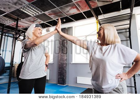 High five. Delighted positive senior women standing opposite each other and giving a high five while being in a great mood