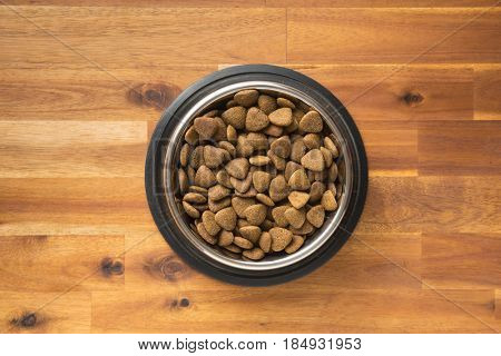 Dry kibble dog food in metal bowl on wooden table. Top view.