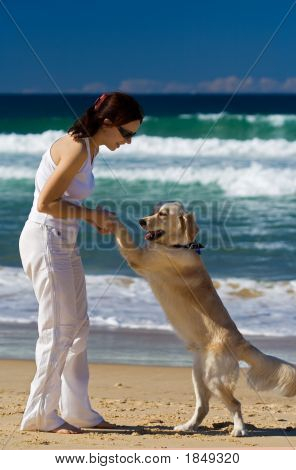 Young female dancing on a beach with a dog poster