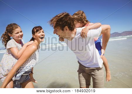 Cheerful parents piggybacking their children at beach against clear blue sky