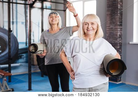 Positive emotions. Happy well built senior women standing together and holding yoga mats while enjoying their time in fitness club