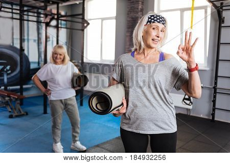 Everything is OK. Joyful active nice woman shoeing OK sign and smiling while holding a yoga mat