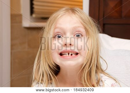 adorable school age girl showing off empty space where baby tooth fell out