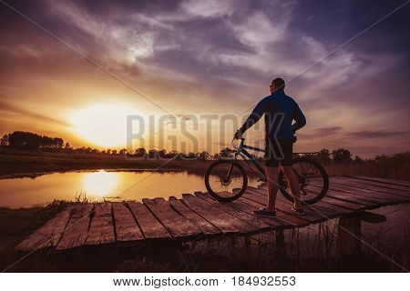 biking. man Rides on a wooden bridge across the river