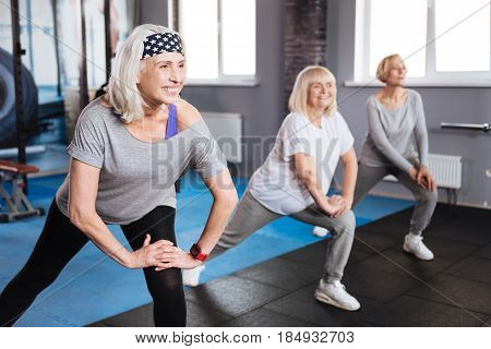 Fitness club. Happy active elderly women standing in a row and doing a physical exercise while visiting a fitness club