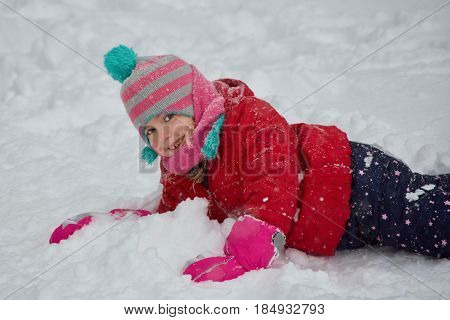 Adorable school age girl playing outside in wintertime