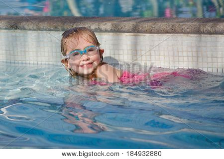 Adorable school age girl wearing goggles and swimming in pool
