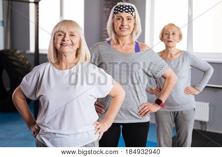 Together it is more interesting. Happy positive senior women standing together and resting hands on the hips while working out together