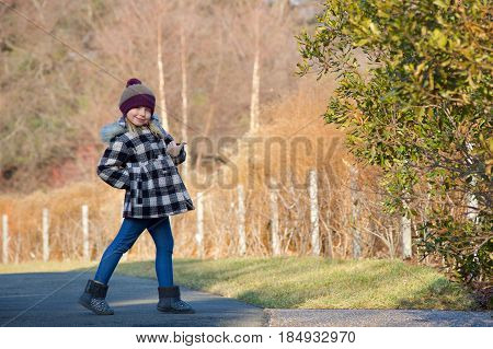 Adorable school age girl standing outside in wintertime giving thumbs up
