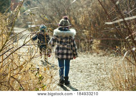 Brother and sister walking together outside in wintertime