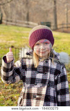 Adorable school age girl with facepaint standing outside in winter coat and hat giving thumbs up