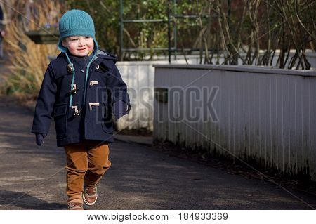 Adorable toddler boy walking outside in winter coat and hat