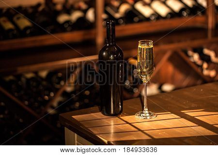 Champagne bottle and glass placed on a wooden table. Shelves with wine bottles on a background.
