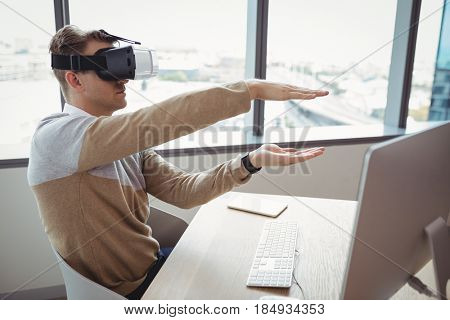 Happy executive using virtual reality headset in office
