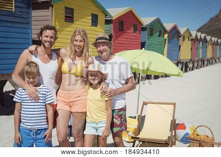 Portrait of multi-generated family standing at beach during sunny day