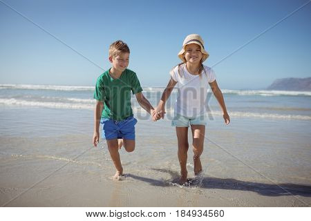 Happy siblings holding hands while running on shore at beach during sunny day