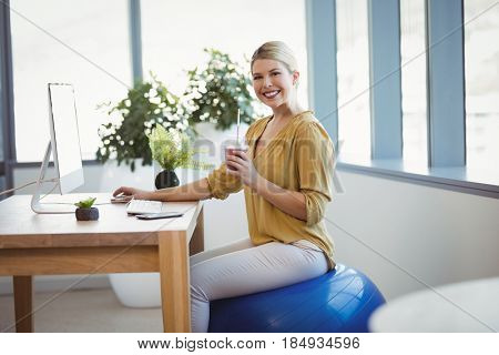 Portrait of smiling executive sitting on fitness ball while working at desk in office